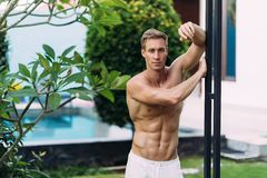 Portrait of sexy athletic man in white pants with naked torso resting in tropical garden. With. Fitness model posing on camera royalty free stock photo