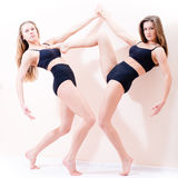 Portrait of 2 sexy attractive young athletic figure women beautiful blond girl friends standing on tiptoe Stock Images