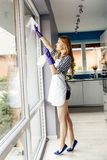 Portrait of attractive young woman cleaning windows in the house Stock Images