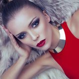 Portrait of blond woman in red dress with fur coat Royalty Free Stock Image