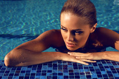 Portrait of sexy blond woman relaxing in swimming pool Stock Images