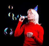 Portrait of a sexy blonde blowing bubbles. Attractive young blond woman blowing bubbles at party. Passion Royalty Free Stock Photos