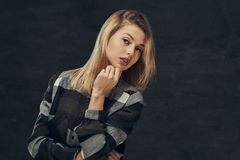 Portrait of a sexy blonde girl in a fleece shirt, posing in a studio. Isolated on a dark background Stock Images
