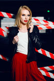Portrait of sexy blonde girl with red lips wearing a rock black style on the background of warning tape. Fashion portrait of sexy blonde girl with red lips Stock Photo