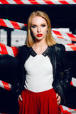 Portrait of sexy blonde girl with red lips wearing a rock black style on the background of warning tape. Fashion portrait of sexy blonde girl with red lips Royalty Free Stock Images