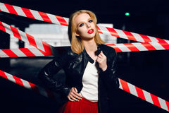 Portrait of sexy blonde girl with red lips wearing a rock black style on the background of warning tape. Fashion portrait of sexy blonde girl with red lips Stock Photography