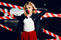 Portrait of sexy blonde girl with red lips wearing a rock black style on the background of warning tape. Fashion portrait of sexy blonde girl with red lips Royalty Free Stock Photos