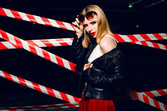 Portrait of sexy blonde girl with red lips wearing a rock black style on the background of warning tape. Fashion portrait of sexy blonde girl with red lips Royalty Free Stock Photo