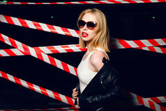 Portrait of sexy blonde girl with red lips wearing a rock black style on the background of warning tape. Fashion portrait of sexy blonde girl with red lips Stock Images
