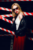 Portrait of sexy blonde girl with red lips wearing a rock black style on the background of warning tape. Fashion portrait of sexy blonde girl with red lips Royalty Free Stock Photography