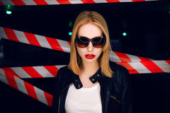 Portrait of sexy blonde girl with red lips wearing a rock black style on the background of warning tape. Fashion portrait of sexy blonde girl with red lips Royalty Free Stock Image