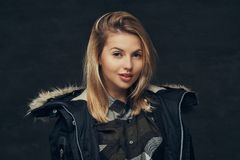 Portrait of a sexy blonde girl in a winter jacket and fleece shirt, standing in a studio. On a dark background Royalty Free Stock Image