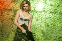 Portrait of sexy blonde  with gun. Against camouflage net Royalty Free Stock Images