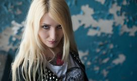 Blonde punk in a leather jacket with rivets and tattoos on her chest. The background is peeling paint on the wall. Portrait of a blonde punk in a leather jacket stock photos