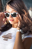 Portrait of sexy brunette girl putting on sunglasses at windy day Royalty Free Stock Photography