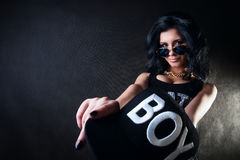 Portrait of sexy brunette in glasses. Swag girl. Sexy brunette holding a hat in his outstretched hands Royalty Free Stock Photo