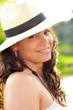 Portrait of a sexy brunette smiling. Close-up portrait of a stunningly sexy brunette wearing a beach hay hat, smiling. Concept about relaxing at the beach Royalty Free Stock Photo