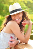 Portrait of a sexy brunette wearing a beach hat. Closeup portrait of a sexy brunette woman wearing a hay summer beach hat while playing with her hair, winking Stock Photography