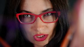 Portrait of a sexy brunette woman with red lips who eroticly and playfully tries on different pairs of stylish. Portrait of a sexy brunette woman with red lips stock footage