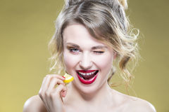 Portrait of Sexy Caucasian Blond Girl Eating Tiny Lemon Piece. Demonstrating Much of Good Taste with Eye Winking. Posing Against Yellow Background.Horizontal Stock Photography