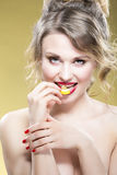Portrait of Sexy Caucasian Blond Girl Eating With Tiny Lemon Piece. Showing Satisfied and Alluring Facial Expression. Against Yellow Background.Vertical Image Stock Image