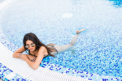 Portrait of cheerful woman relaxing at the luxury poolside. Girl at travel spa resort pool. Summer vacation. Stock Images