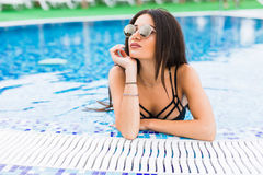 Portrait of cheerful woman relaxing at the luxury poolside. Girl at travel spa resort pool. Summer vacation. Royalty Free Stock Image