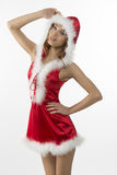Portrait of sexy christmas girl. With short red dress and fur hood, in sensual pose smiling and looking in camera Royalty Free Stock Photo