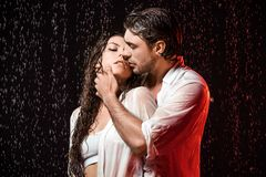 portrait of sexy couple in white shirts standing under rain