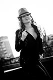 Portrait of sexy curly woman in hat standing on rooftop Stock Images