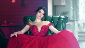 Portrait of sexy fashion woman in red evening glamour dress sitting on armchair looking at camera stock video