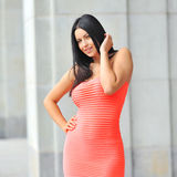 Portrait of sexy female model in red dress posing outdoor Stock Photos