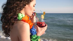Portrait of sexy girl on beach, summer vacation, women looking at sea ocean and drinking cocktail,. Wind developing hair of happy young woman with Hawaiian Lei stock video footage