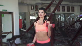 Portrait of girl doing exercise with dumb-bells in the gym. In full HD stock video footage