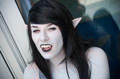 Portrait of sexy girl with dracula teeth and pointed ears at the geek cosplay convention