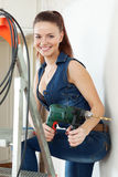 Portrait of sexy girl in overalls with drill Royalty Free Stock Photography