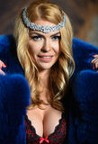 Portrait of sexy glamour woman with long blond hair wearing luxurious blue fur coat and seductive red lingerie. Royalty Free Stock Photos
