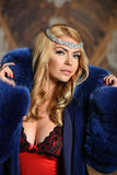 Portrait of sexy glamour woman with long blond hair wearing luxurious blue fur coat and seductive red lingerie. Stock Photography