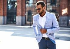 Handsome modern businessman posing on street background stock photos