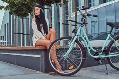 Portrait of a sexy hippie female wearing blouse and shorts in a headband, sits barefoot on a bench near city bike. Against a skyscraper Royalty Free Stock Photos