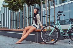 Portrait of a sexy hippie female wearing blouse and shorts in a headband, sits barefoot on a bench near city bike. Against a skyscraper Royalty Free Stock Images