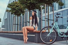 Portrait of a sexy hippie female wearing blouse and shorts in a headband, sits barefoot on a bench near city bike. Against a skyscraper Stock Photo