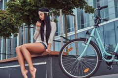 Portrait of a sexy hippie female wearing blouse and shorts in a headband, sits barefoot on a bench near city bike. Against a skyscraper Royalty Free Stock Image