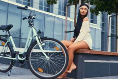 Portrait of a sexy hippie female wearing blouse and shorts in a headband, sits barefoot on a bench near city bike. Against a skyscraper Stock Photos