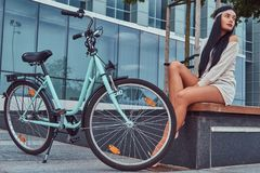 Portrait of a sexy hippie female wearing blouse and shorts in a headband, sits barefoot on a bench near city bike. Against a skyscraper Stock Image