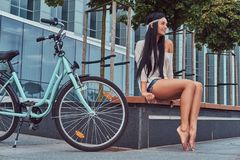 Portrait of a sexy hippie female wearing blouse and shorts in a headband, sits barefoot on a bench near city bike. Portrait of a sexy smiling hippie female Royalty Free Stock Images