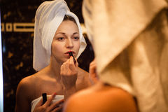 Portrait of hot lady in panties and lipstick in the bathroom looking in the mirror. Hot young lady in panties and lipstick in the bathroom looking in the mirror royalty free stock image