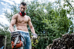 Portrait of sexy man with chainsaw and protective gear ready Stock Photography