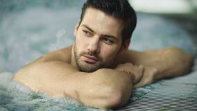 Portrait of sexy man enjoying in whirlpool bath. Handsome guy relaxing in pool