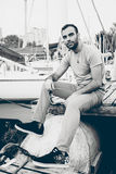 Portrait of sexy man sitting on pier at port with yachts Stock Photography